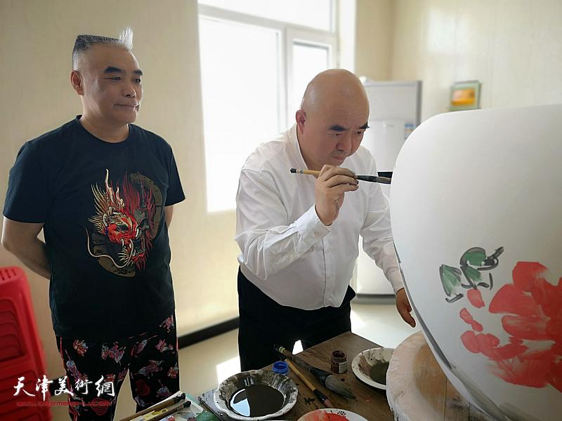 著名书画家尹沧海在北方陶艺中心创作青花瓷。旁为德谦文化科技发展有限公司董事长、北方陶艺中心艺术总监王树江。