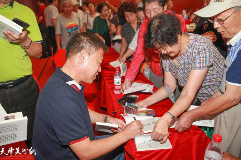 刘存发先生在首发式现场为读者签名留念。