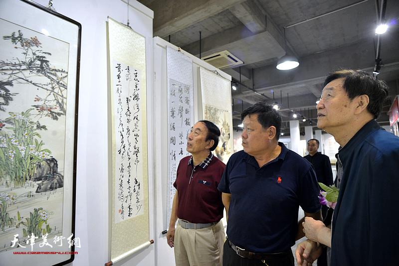 张金方、李岳林、郭鸿春在展览现场观看作品。