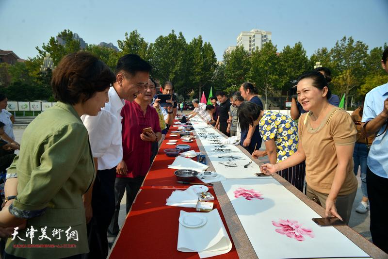 区、街有关领导在书画长卷创作现场与书画家见面交流。