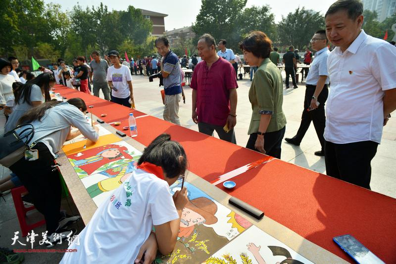区、街有关领导在书画长卷创作现场观赏小画家们创作。