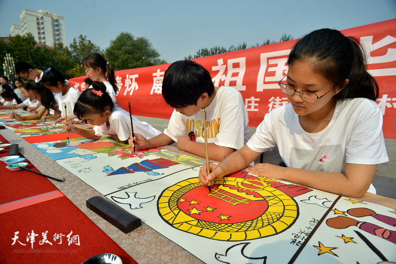 """十月书画院小学员及家长创作""""爱祖国,庆丰收""""为主题的20米长卷。"""