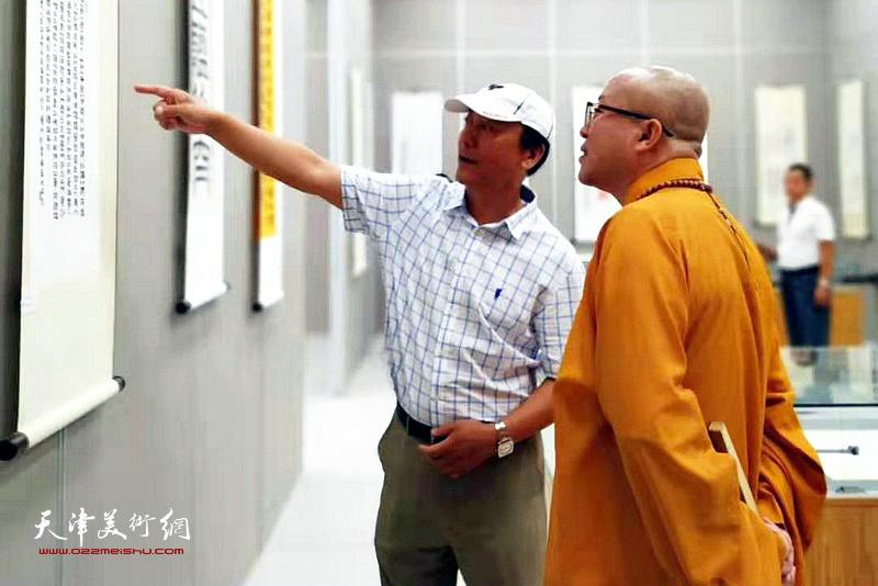 张福义向智如法师介绍作品。