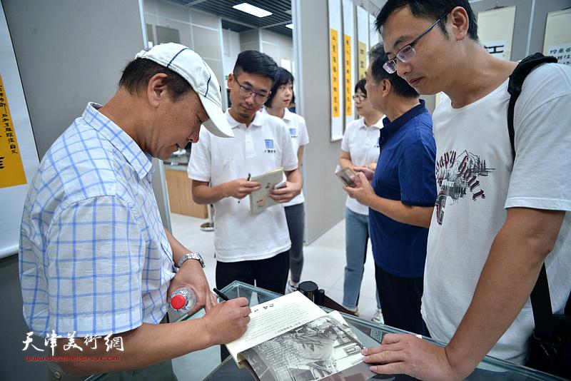 张福义在展览现场为书画爱好者杨颖签名留念。