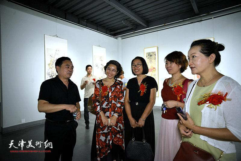 黄勇与参展的女画家在展览现场交流。