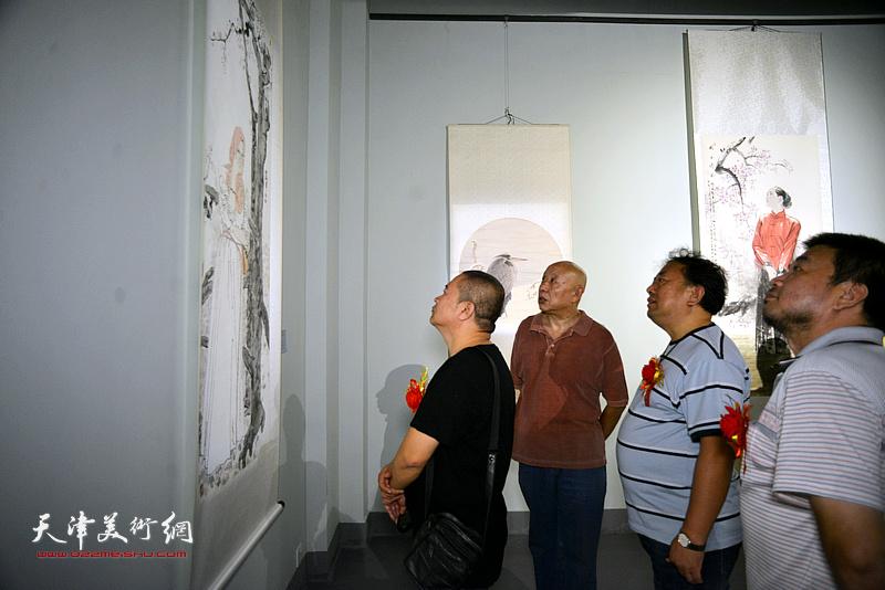 高建章、宋世凯、田军在展览现场观看展品。