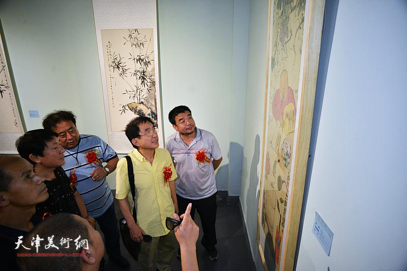 王文元、主云龙、高建章、田军在展览现场观看展品。