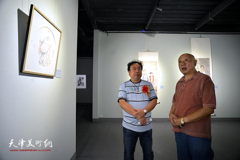 高建章在展览现场观看展品。