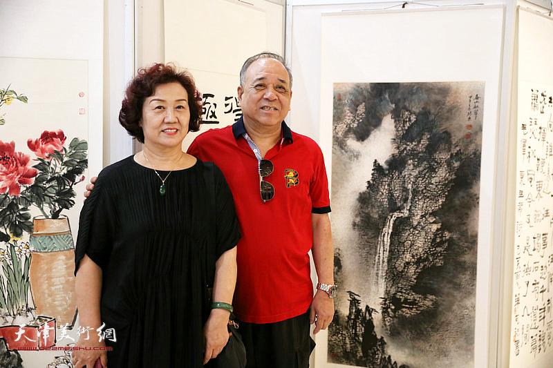 参展作者郭振东夫妇在展出的作品前。