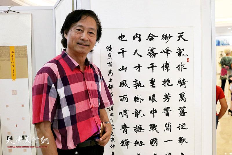书法家韩天宏在自己的参展作品前。