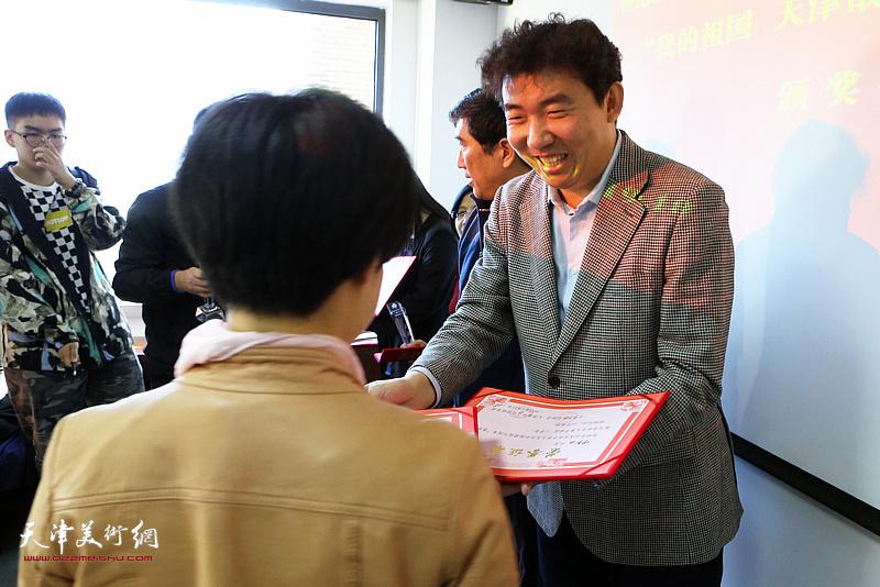 春秋文化传媒集团董事长王健为获奖作者颁发二等奖。
