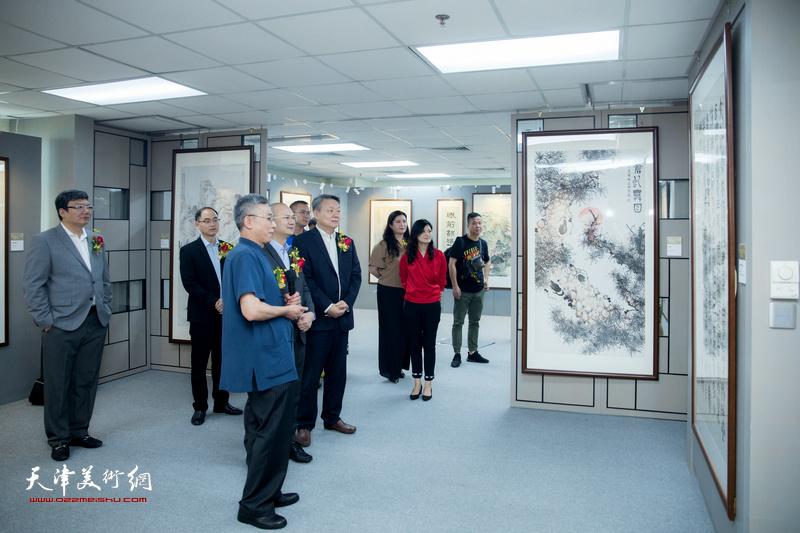 杨维陪同嘉宾在观看展出的作品。