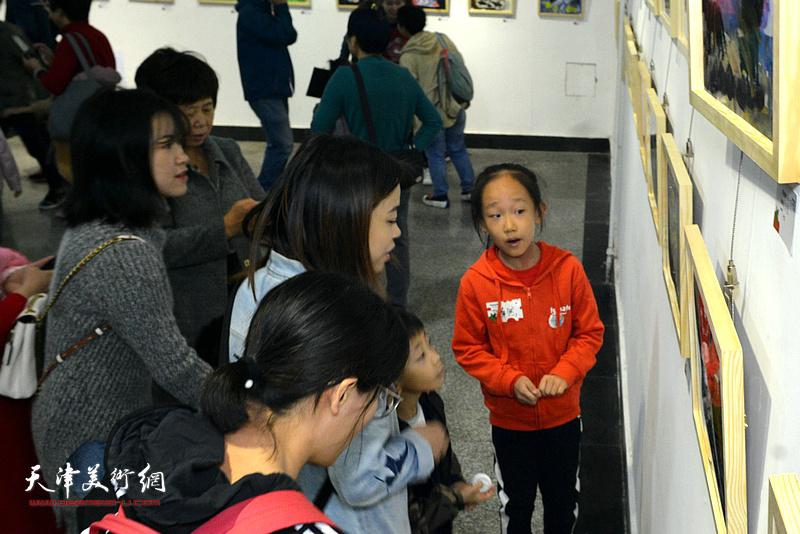"""义务小讲解员在""""消失的动物""""大型环保主题艺术创作展现场做讲解。"""