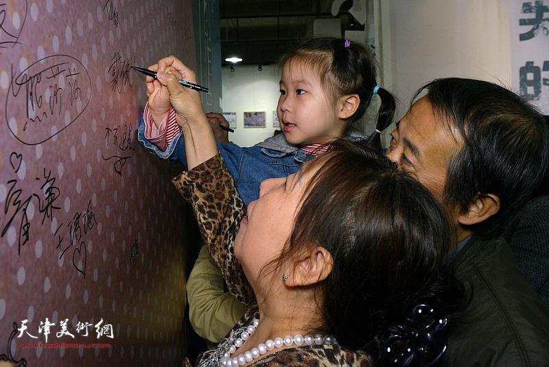 小朋友在活动现场的签名墙上签名留念。