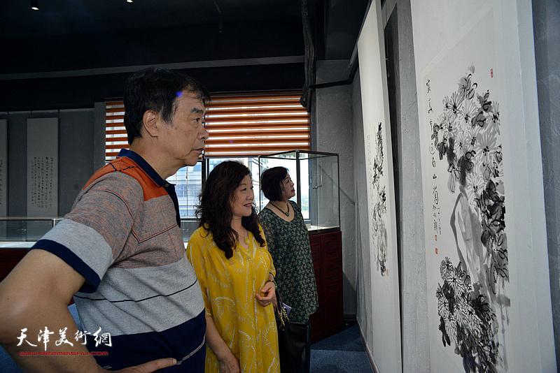 著名文化学者姜维群先生观赏展出的作品。