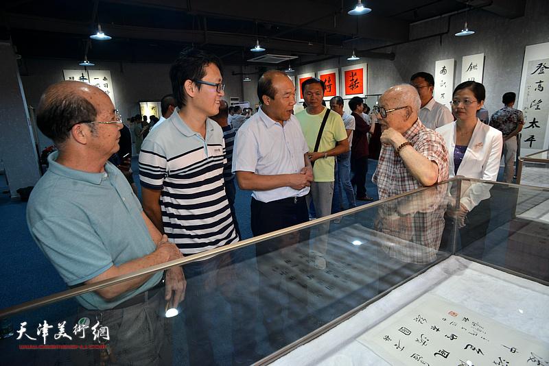 王树秋陪同吴兆奇、黄少兰等嘉宾观赏展出的作品。