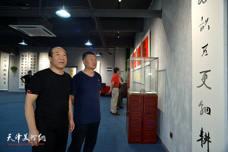 王树秋与窦宝铁观赏展出的作品。