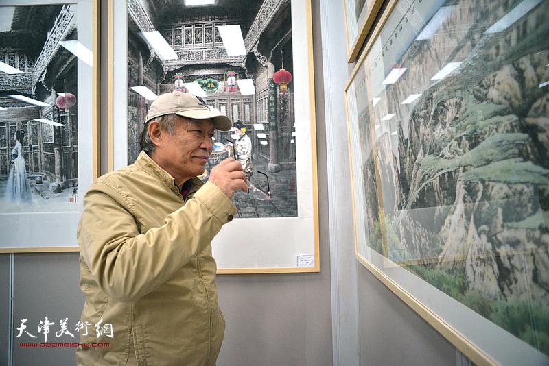 何延喆在画展现场观看作品。