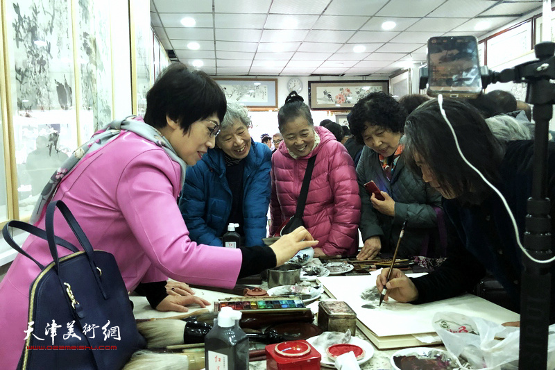 翟洪涛在画展现场与书画爱好者交流画艺。
