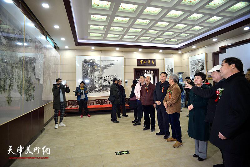 陈秀华、李洪强、杨华山、孟庆占、洪潮、周振亮在画展现场观看作品。
