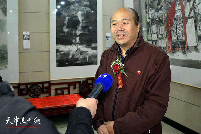 孟庆占在画展现场接受媒体采访。
