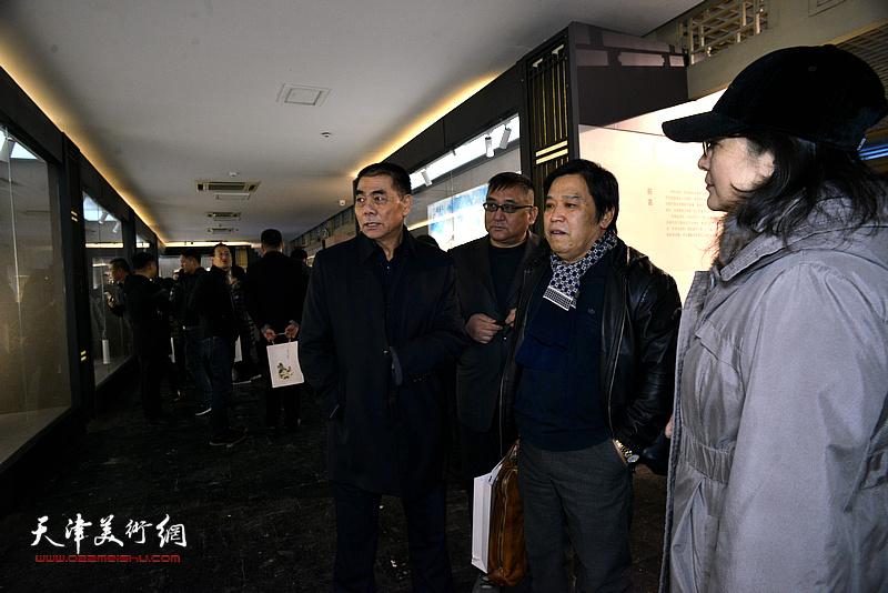 张根起向李耀春、杨文介绍展出的作品。