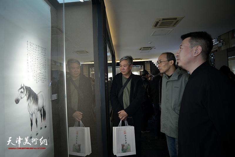 薛海强、王强等观赏展出的作品。