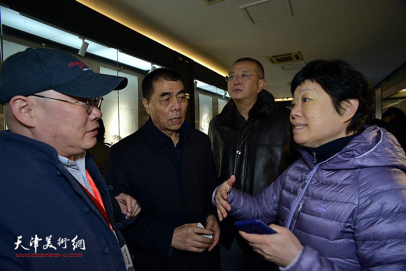 张根起与龚军等在画展现场交流。
