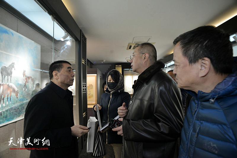 张根起与来宾在画展现场交流。
