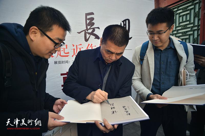 张根起为来宾在《松风长迴——张根起近作展作品集》上签名留念。