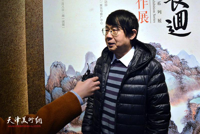 毓岳向媒体介绍张根起的艺术。