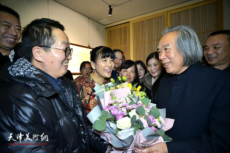 图为学生们向霍春阳教授献花,祝贺画展举办成功。