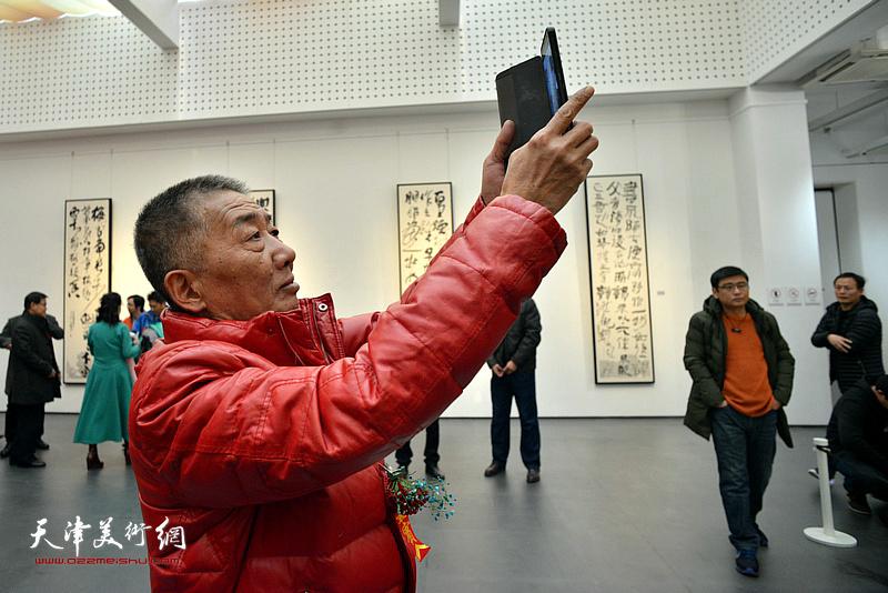 邓国源将展出的作品拍下来。