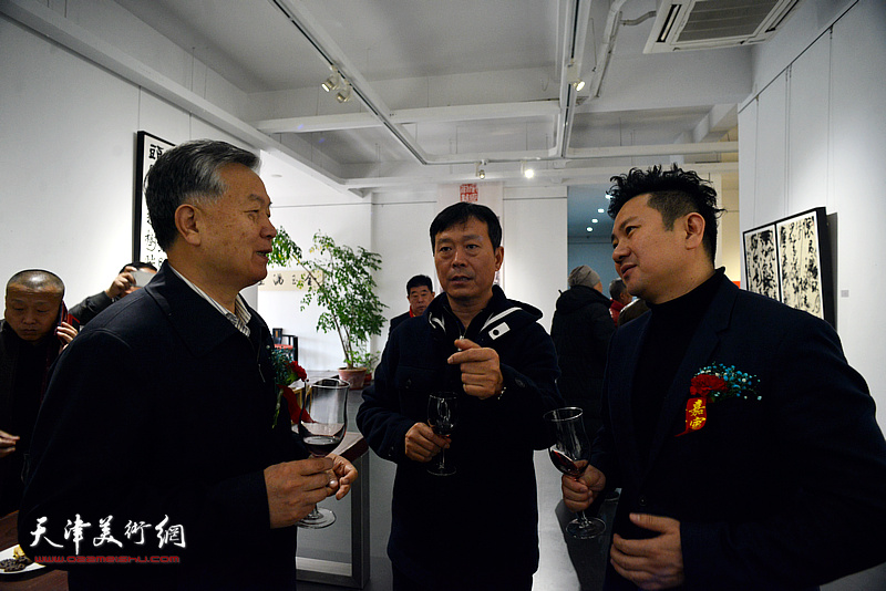 曹育民将军与朱懿、石磊在展览现场交谈。