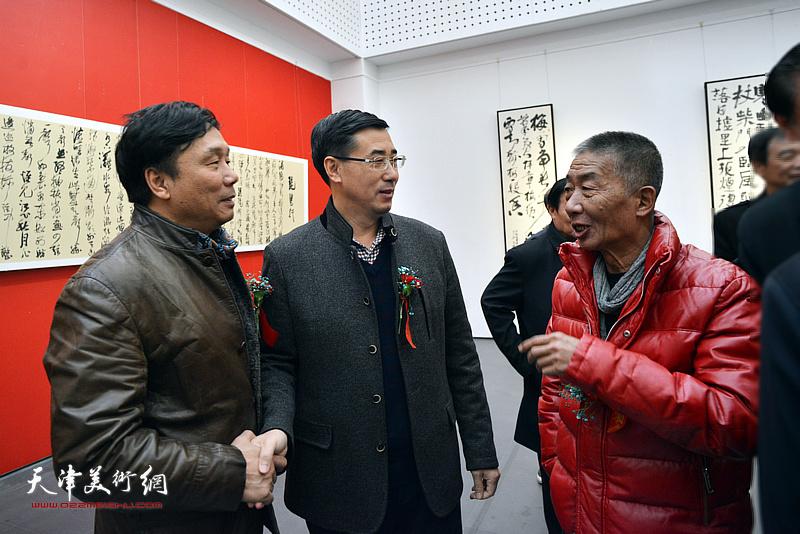 邓国源与王琨、王月周在展览现场交谈。