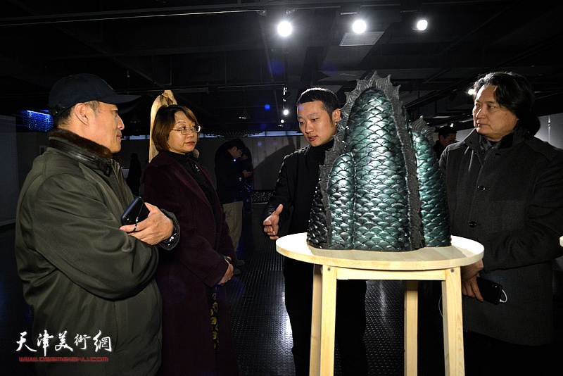 参展作者许楠向孙杰、王学斌介绍展出的作品。
