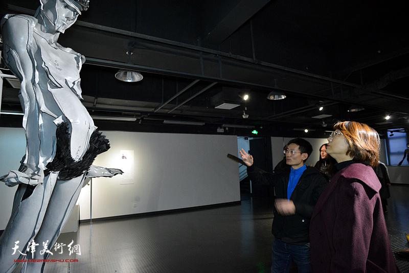 参展作者胡庆雁向孙杰、王学斌介绍展出的作品。