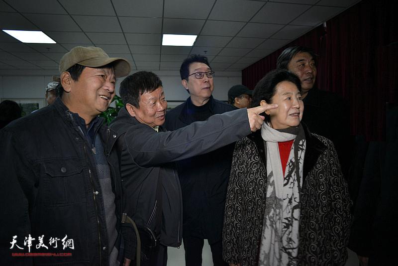 帅起向曹秀荣介绍展出的作品。