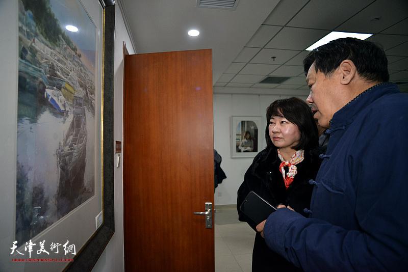 郭鸿春、朱彤观看展出的作品。