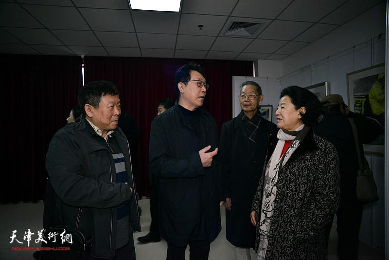 曹秀荣、刘建华、刘书翰、帅起在画展现场交流。