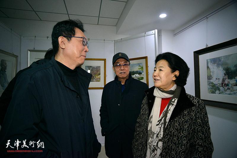 曹秀荣、崔志强、刘书翰在画展现场交流。