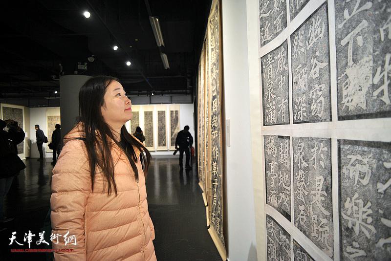 訾春花在展览现场观看展品。