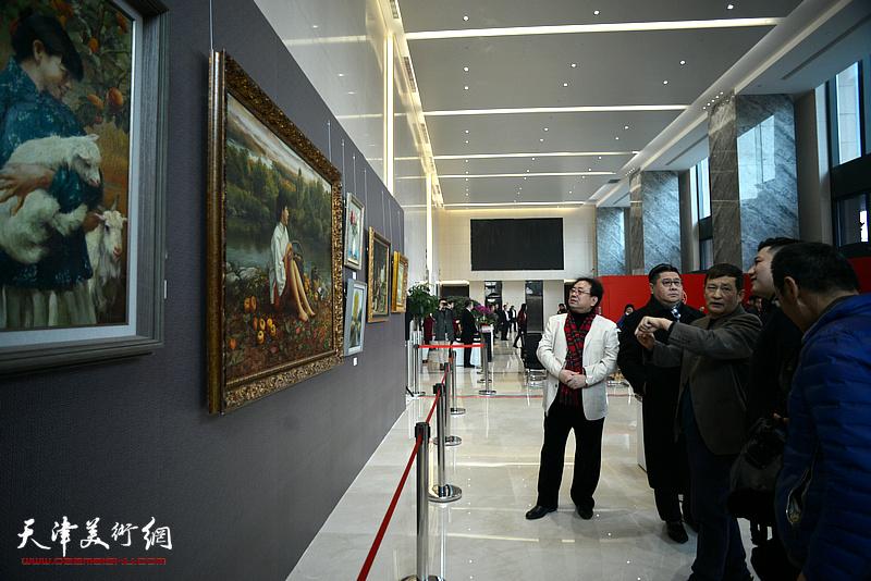 高建章与王志民、杨勐等观赏展出的油画作品。