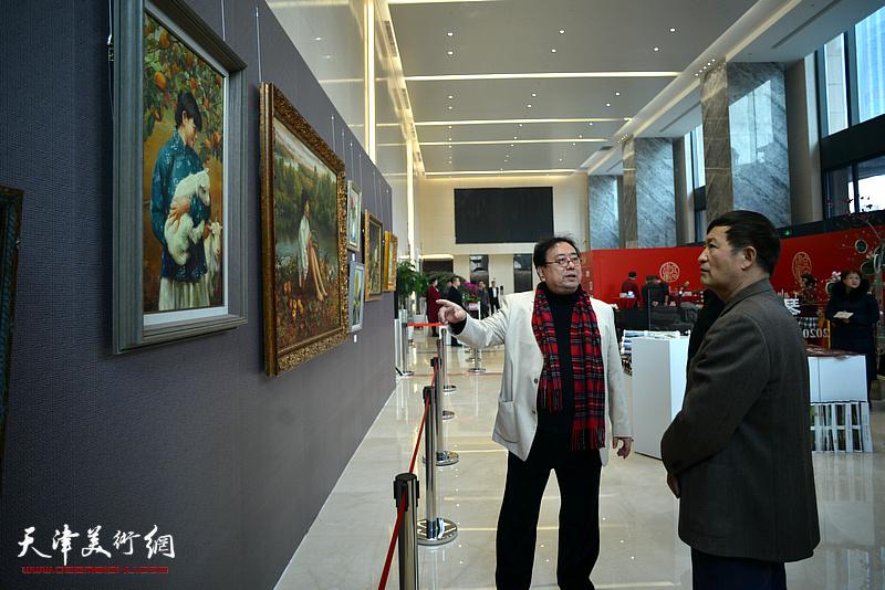 高建章向王志民介绍展出的油画作品。