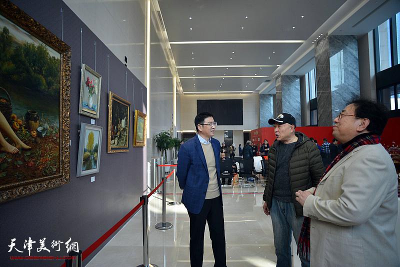 高建章与陈列伟等观赏展出的油画作品。