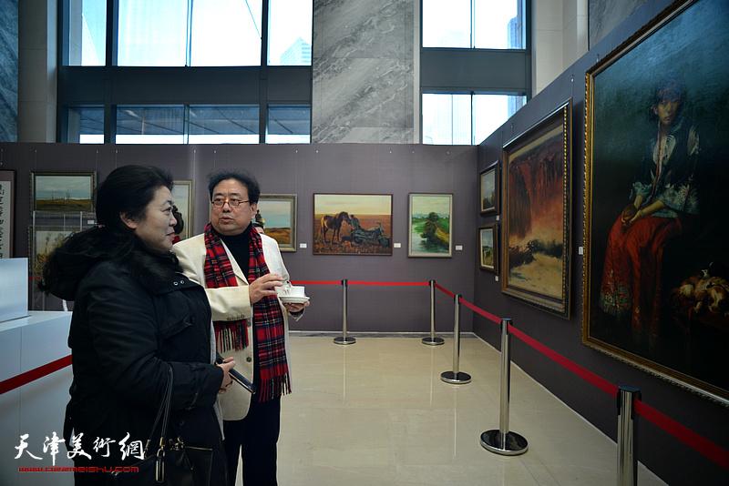 高建章向观众介绍展出的油画作品。