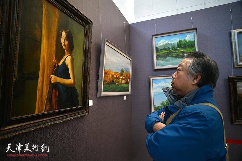 石增琇在观赏展出的油画作品。