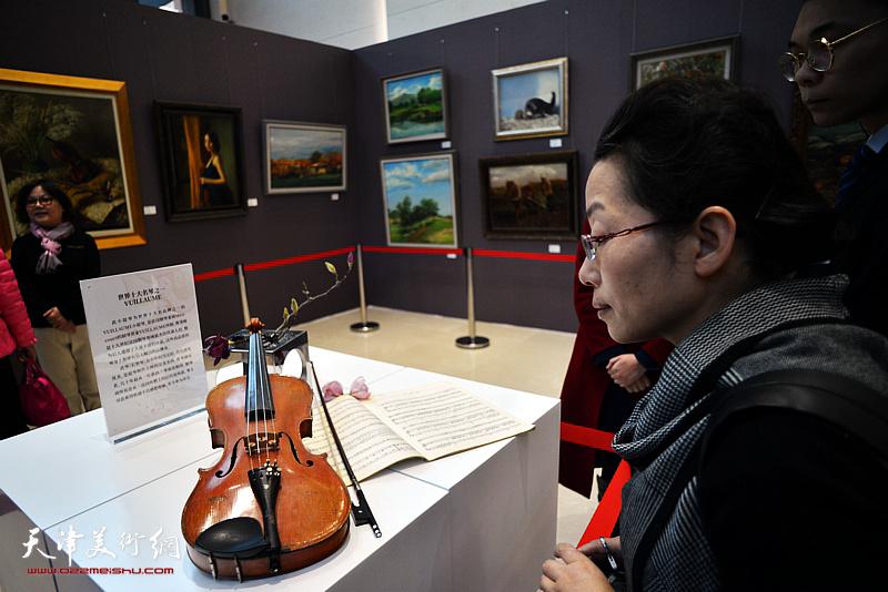 观众在画展现场观赏展示的小提琴名琴。