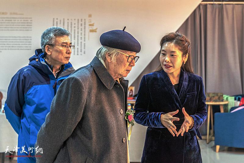 杨维陪同华非观赏展出的作品。