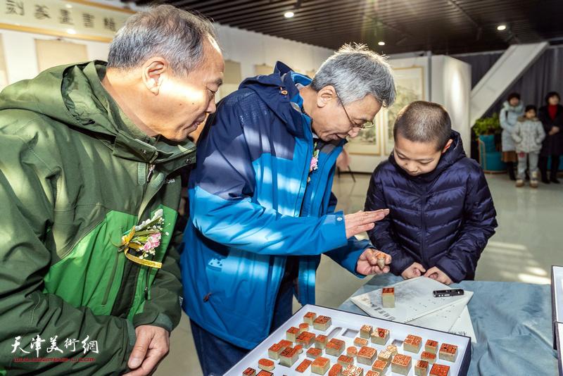 杨维为小观众介绍展出的作品。
